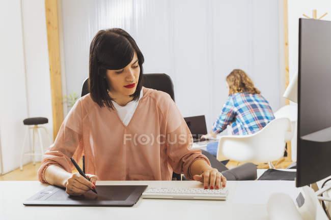 Fille à l'aide d'une tablette graphique au bureau — Photo de stock