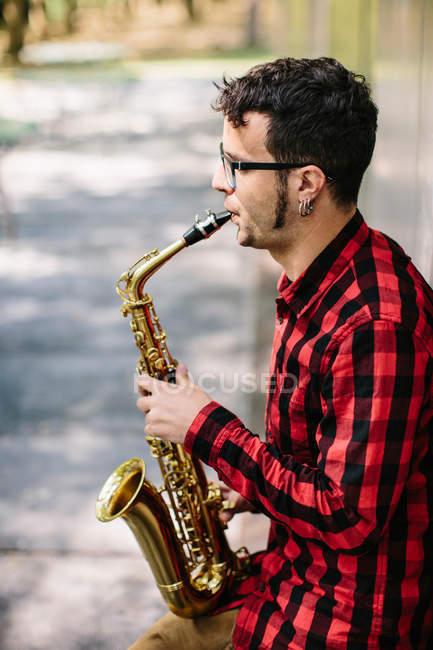 Sassofonista appoggiato al muro e che suona il sax — Foto stock