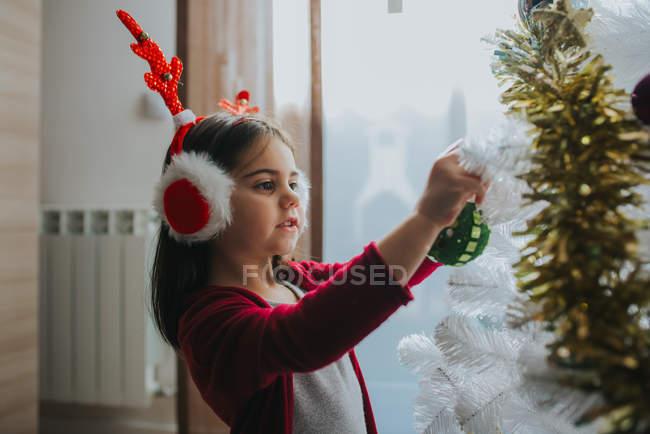 Vista laterale di una ragazza adorabile indossando paraorecchie di pelliccia di Natale con i antlers immissione Bagattelle sul albero di Natale decorativo — Foto stock