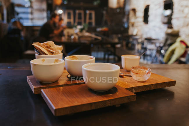 Close up view of dirty bowls with leftovers at empty table at cafe — Stock Photo