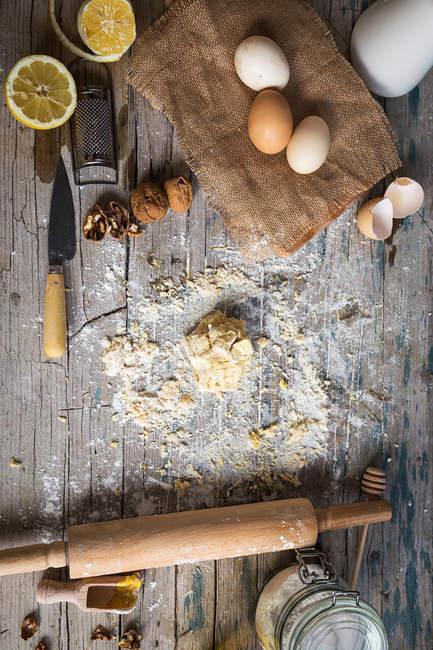 Draufsicht der Bäckerei Zutaten und Geschirr auf rustikalen Holztisch — Stockfoto
