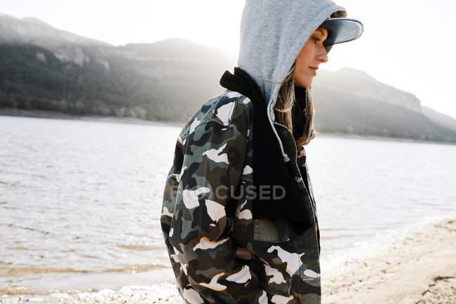 Вид сбоку молодой стильной девушки в пальто и кепке на фоне озера и гор . — стоковое фото