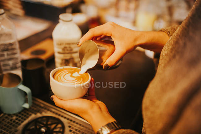 Over shoulder view of baristas hands mixing coffee and cream in cappuccino cup. — Stock Photo