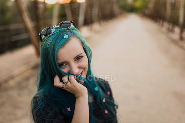 Girl with confetti in blue hair looking at camera — Stock Photo