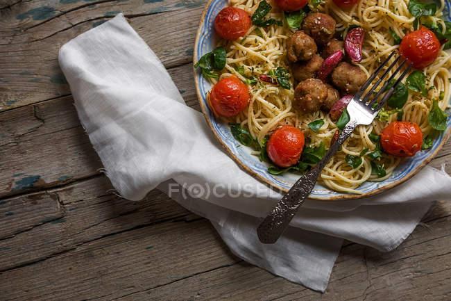 Обрізати зображення макарони з фрикадельки та помідорів чері на плиті служили на рушник більш дерев'яний стіл — стокове фото