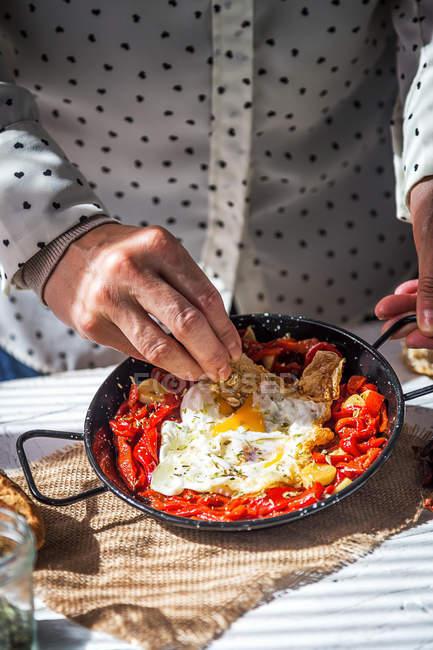 Section médiane mettant l'ingrédient dans la poêle avec des oeufs brouillés et tomates séchées — Photo de stock