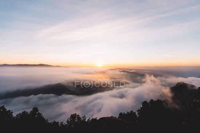 Vista aérea de cloudscape nas montanhas ao pôr do sol — Fotografia de Stock