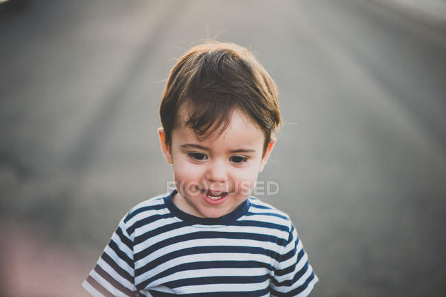 Портрет мальчика, улыбающегося на асфальтированной дороге — стоковое фото