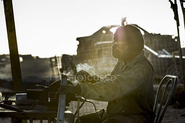 Mann sitzt und schweißt — Stockfoto