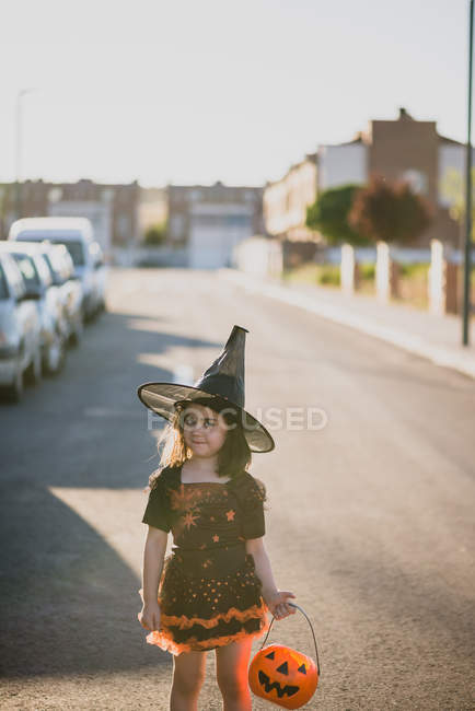 Jeune fille en costume de sorcière debout sur rue — Photo de stock