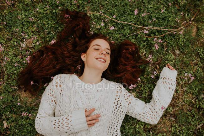 Ragazza sognante che si trova sulla terra con ramo di fioritura e sorridente — Foto stock