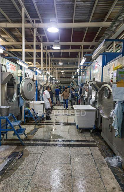 TANGIER, MARRUECO- 18 de abril de 2016: Máquinas industriales en líneas y trabajadores de la confección fabrica - foto de stock