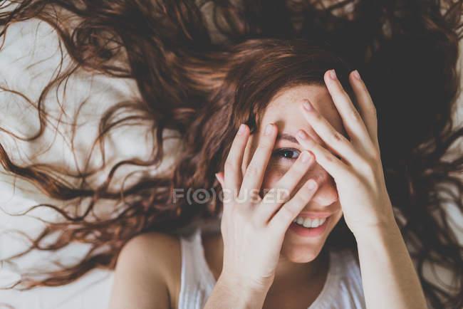 Femme de gingembre en regardant la caméra entre les doigts — Photo de stock