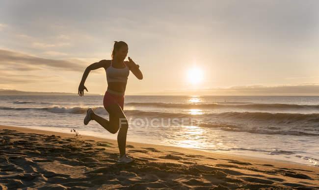 Фітнес жіночий силует працює на пляжі — стокове фото