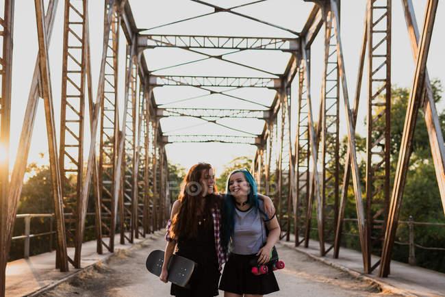 Girls hugging on bridge — Stock Photo