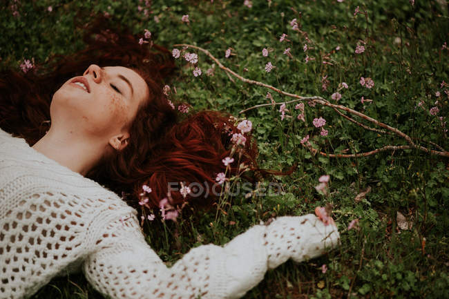 Dreamy girl lying on ground with blooming branch — Stock Photo