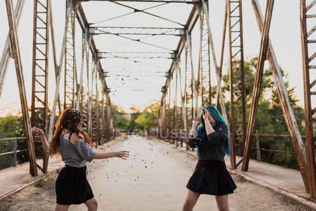 Chicas lanzando confeti en puente - foto de stock