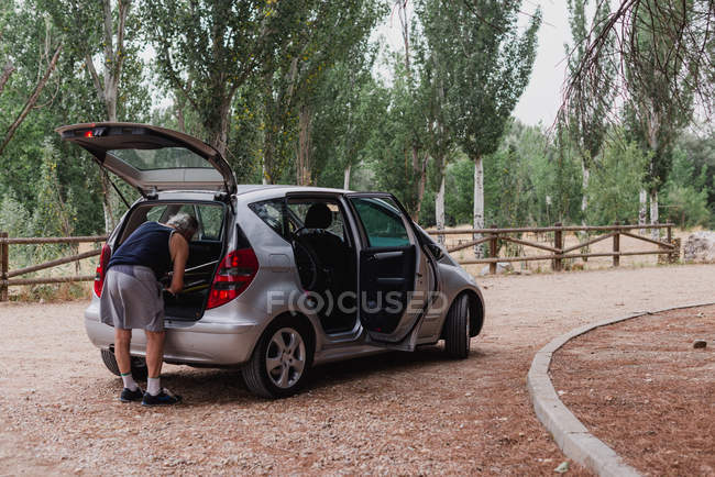Back view of elderly man putting bicycle in car trunk at countryside road — Stock Photo