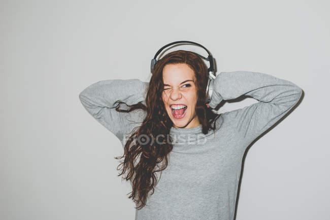 Donna in cuffie che gode della musica con la bocca aperta — Foto stock