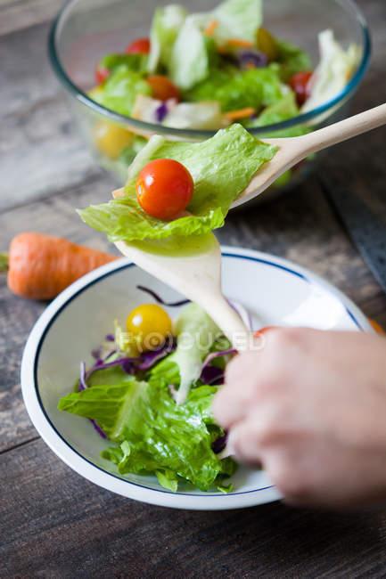 Урожай руками держась ложки салат овощи над чашей — стоковое фото