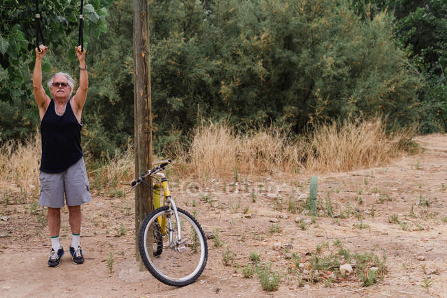 Portrait of elderly man on chin-up bar with bicycle in countryside — Stock Photo