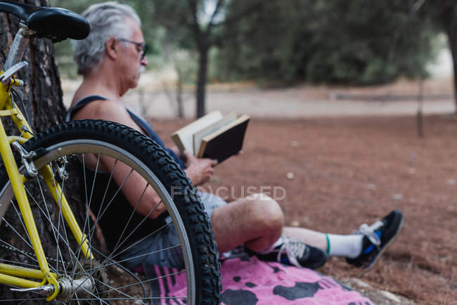Side view of elderly man reading book while sitting on ground in forest beside bicycle — Stock Photo