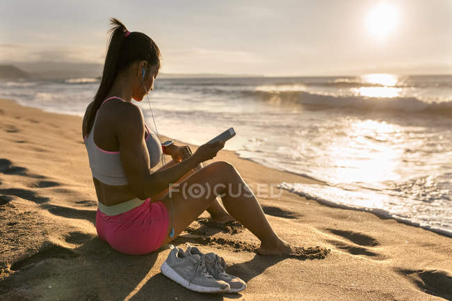 Woman sitting on sand and using smartphone — Stock Photo