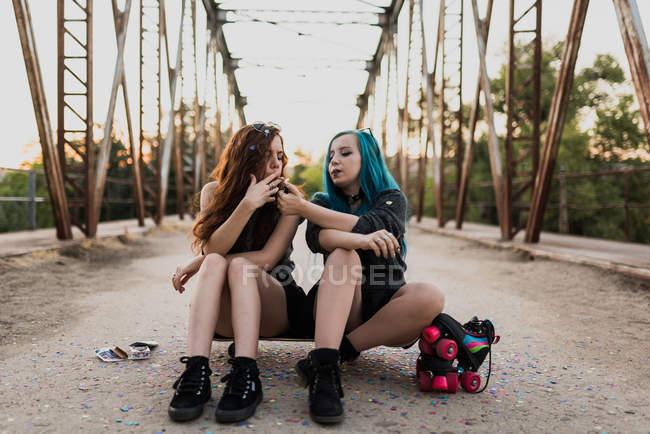 Girls sitting on skateboard and smoking joint — Stock Photo