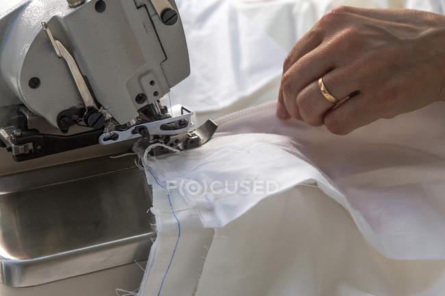 Mão feminina de colheita costura tecido branco — Fotografia de Stock