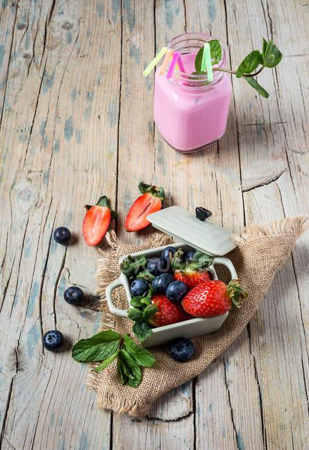Batido em jarra com morangos e mirtilos em tigela na mesa de madeira — Fotografia de Stock