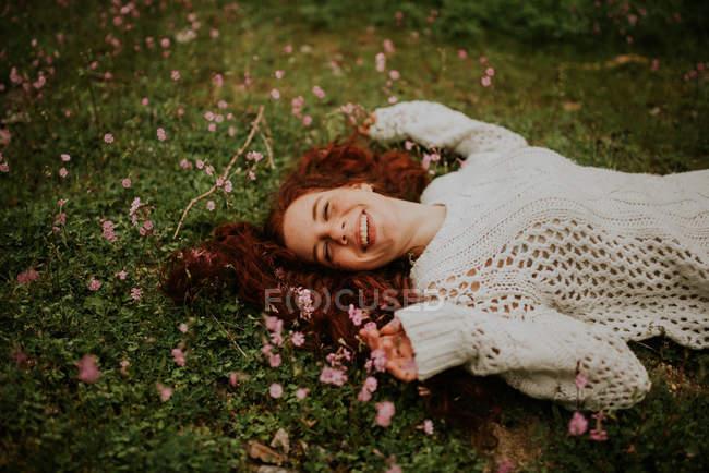 Мечтательная девушка лежит на земле с цветущими цветами — стоковое фото