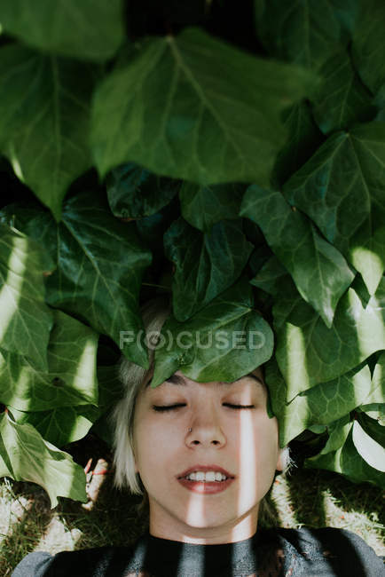 Girl lying on green leaves with eyes closed — Stock Photo