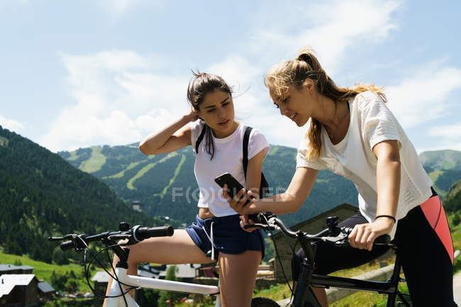 Girls on bicycles using smartphone at mountain road — Stock Photo