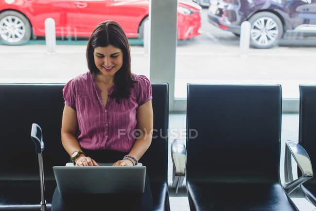 Фронтальний вид smilling дівчина сидить на стілець в зал очікування і використання ноутбук на колінах — стокове фото