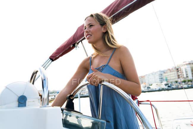Portrait de jeune fille blonde posant à barre sur yacht — Photo de stock