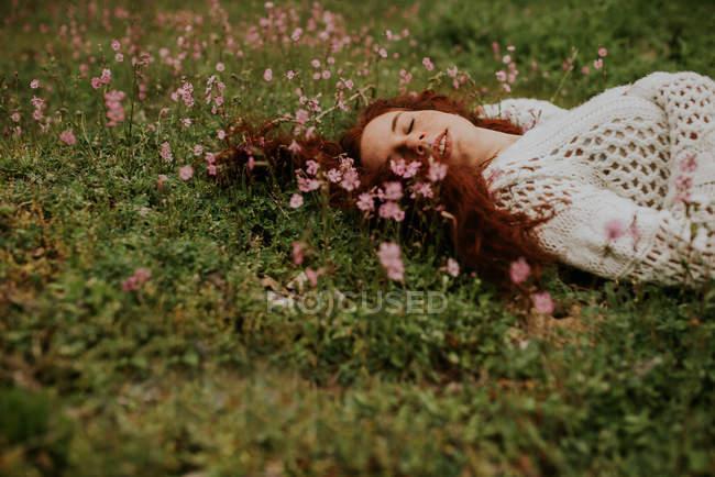 Menina sonhadora, com os olhos fechados, deitado no chão com flor — Fotografia de Stock