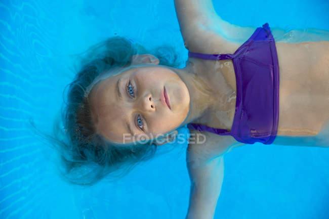 Retrato de criança flutuando na piscina com água turquesa — Fotografia de Stock