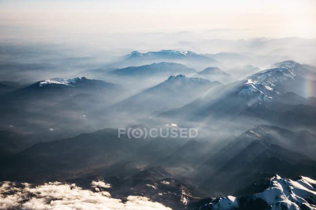 Vista aérea de los rayos de sol sobre las montañas brumosas - foto de stock