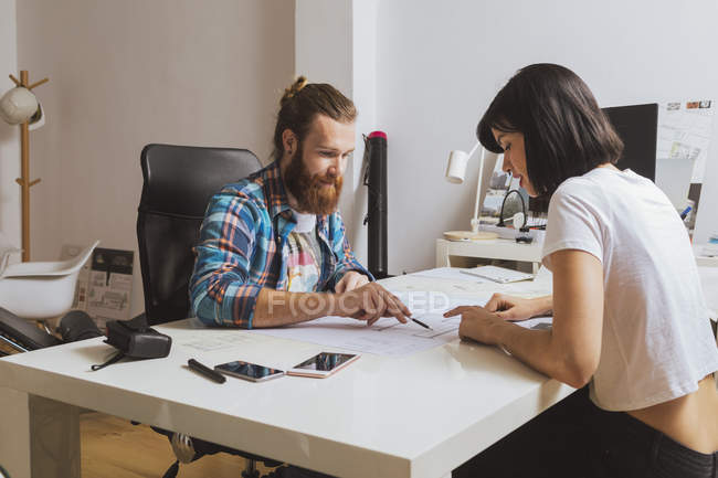 Man and woman sitting over blueprint — Stock Photo