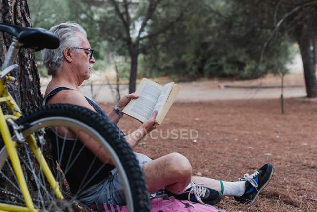Vista laterale del libro di lettura uomo anziano mentre seduto a terra nella foresta accanto alla bicicletta — Foto stock