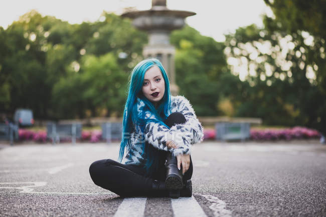 Portrait of blue haired girl sitting on asphalt road and flirtatious looking at camera — Stock Photo