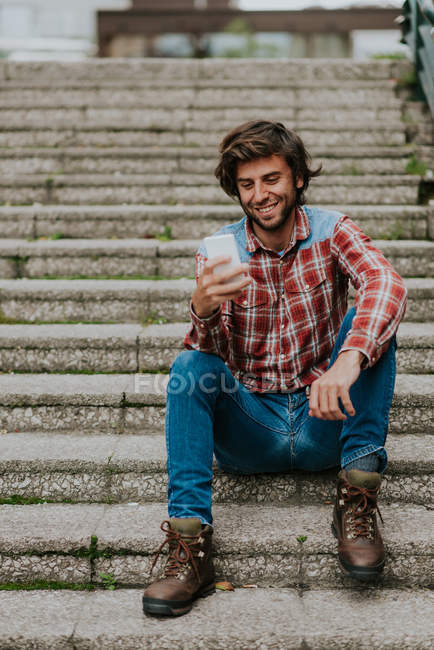 Bearded man in smiling while looking in smartphone on street steps — Stock Photo