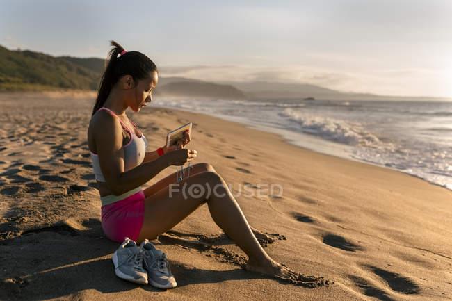 Mulher sentada na areia na praia — Fotografia de Stock