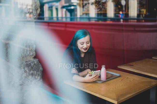 Retrato de menina com cabelo azul, sentado à mesa de café e usando smartphone — Fotografia de Stock