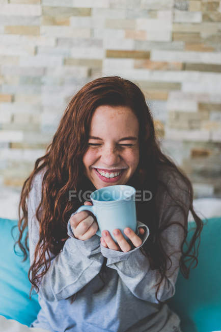 Girl holding blue mug and laughing — Stock Photo
