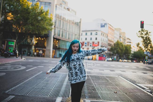 Porträt eines blauhaarigen Mädchens, das mit halb erhobenen Armen geht und auf die urbane Szene herabblickt — Stockfoto