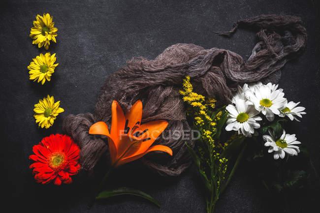 Креативный цветочный узор с несколькими цветками и коричневой газировкой на темной поверхности — стоковое фото