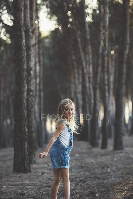 Criança feliz posando na floresta e olhando sobre o ombro para a câmera enquanto mostra a língua — Fotografia de Stock
