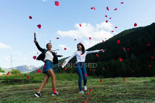 Women having fun with confetti at green meadow — Stock Photo