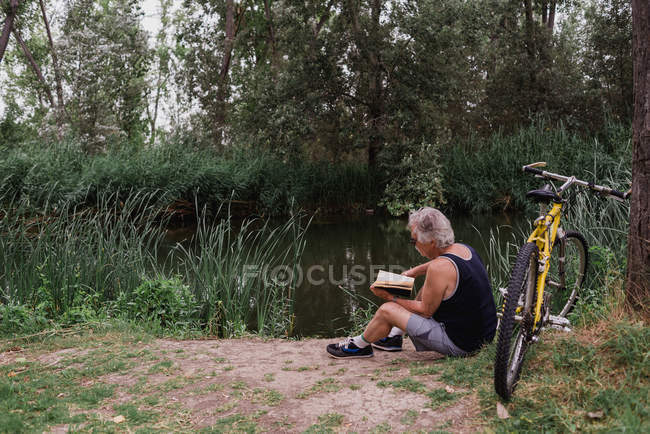 Side view of elderly man reading book while sitting on ground near bicycle at forest river shore — Stock Photo